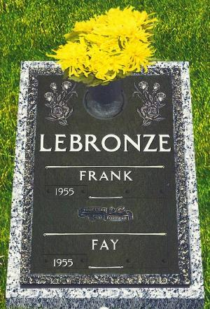 double interment bronze headstone on granite base with rose design and flower vase