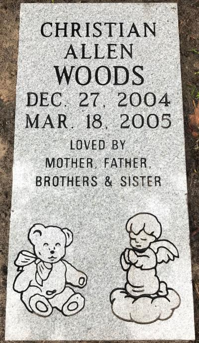 gray granite infant headstone with a teddy bear and praying angel