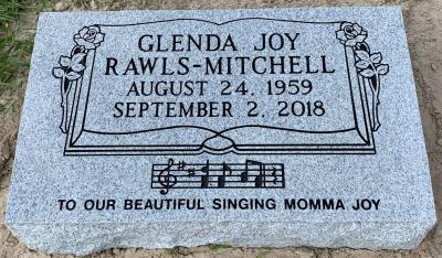 individual gray granite headstone with Bible and Roses Panel and a Musical Notes Emblem