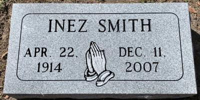 individual gray granite headstone with praying hands and a rounded corner panel design