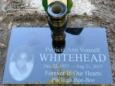 individual jet black granite headstone with laser etching and a granite flower vase