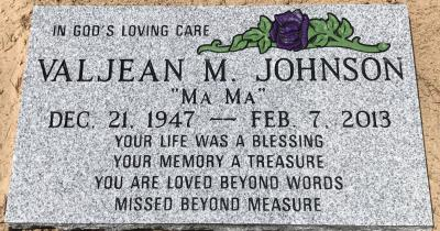 gray granite headstone with a purple rose emblem