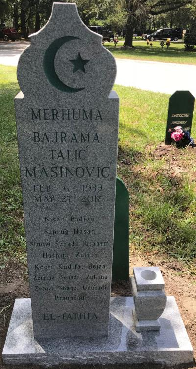 individual granite headstone with crescent moon design and a flower vase
