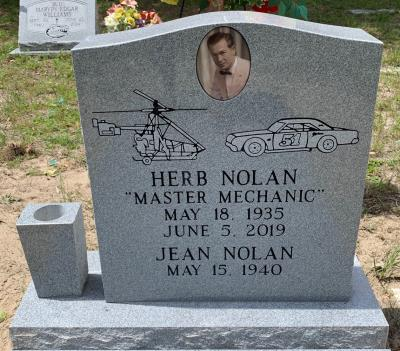 single upright gray granite headstone with race car and helicopter emblems