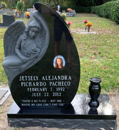individual upright black granite headstone in the shape of an angel and tear drop with a portrait and flower vase